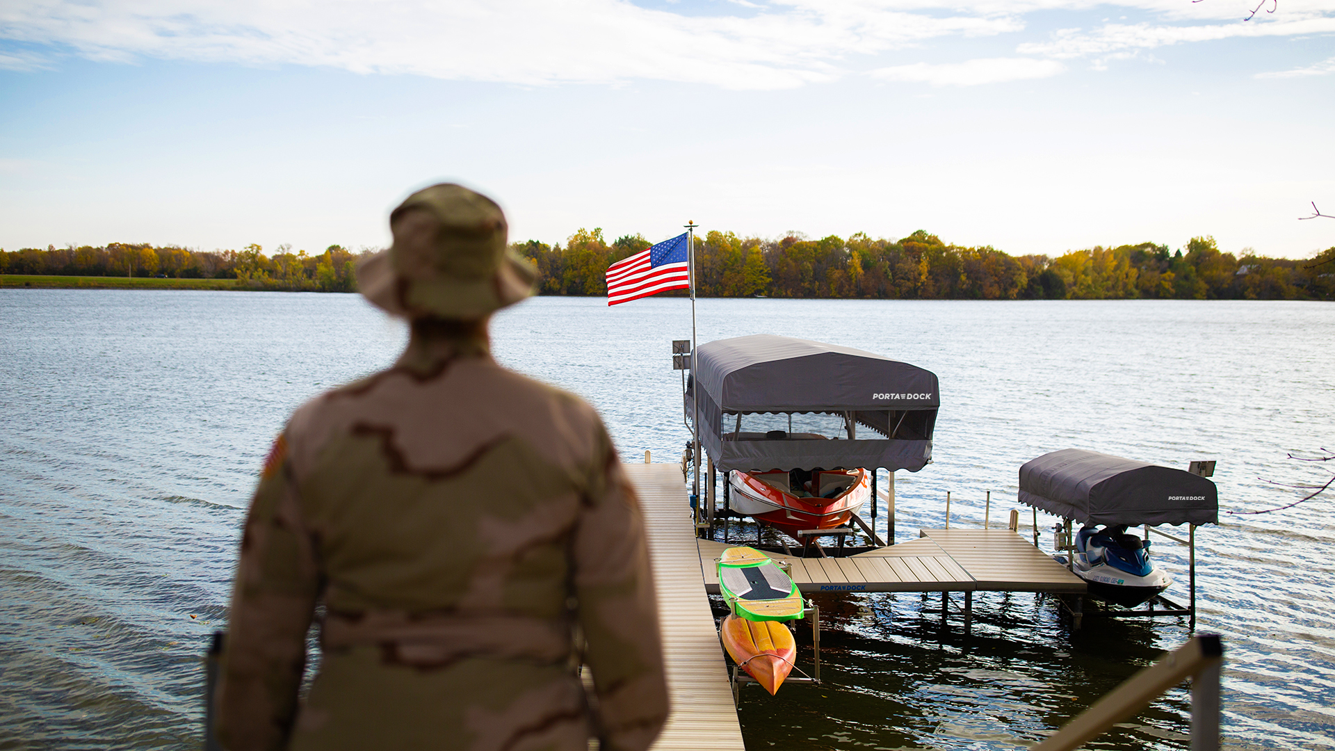Military member and American flag on a Porta-Dock post dock