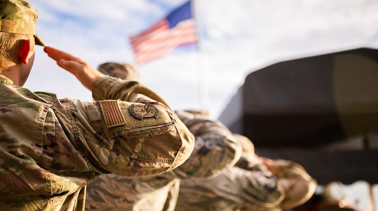 Military members saluting the American flag